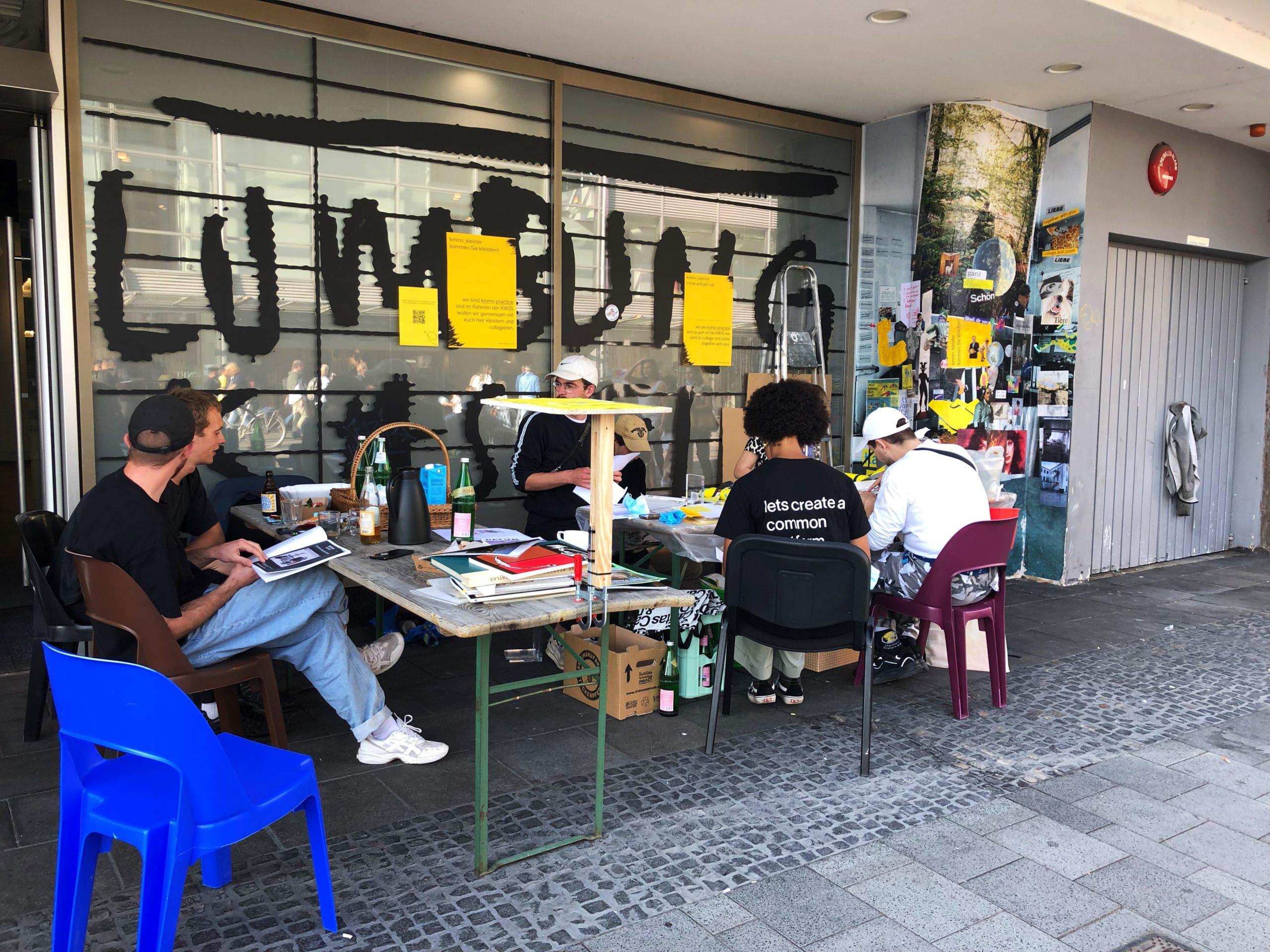 Das Foto zeigt mehrere Menschen, sie sitzen an zwei Biertischen, die am Straßenrand stehen. Auf den Tischen liegen verschiedene Materialien, die Menschen schneiden Material aus und reden miteinander. Rechts ist eine Plakatsäule mit tapeziertem Material sichtbar.