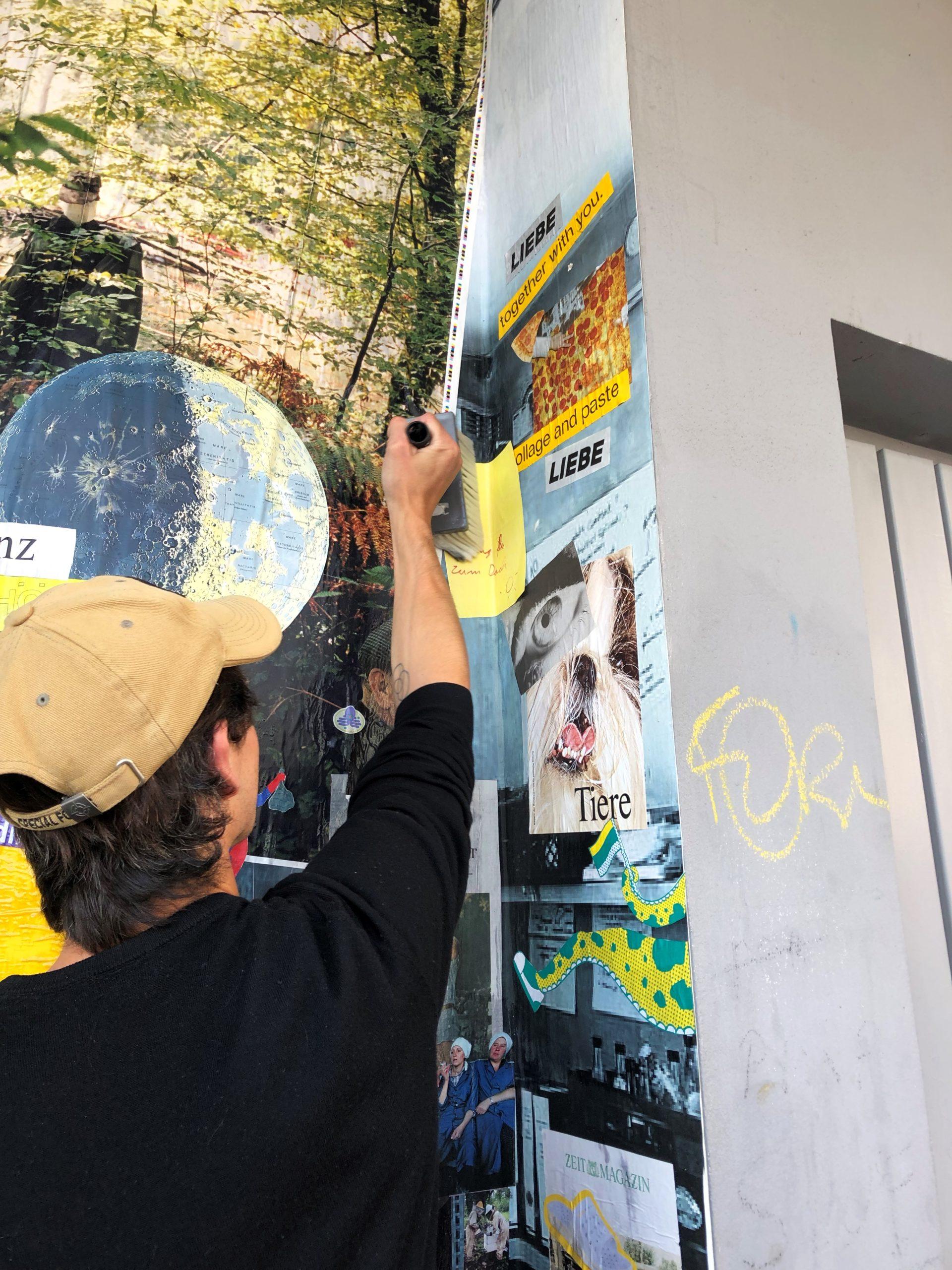 Das Foto zeigt einen Mann von hinten, der mit einem breiten Pinsel über eine Wand streicht, an der verschiedene ausgeschnittene Bilder und Texte kleben.