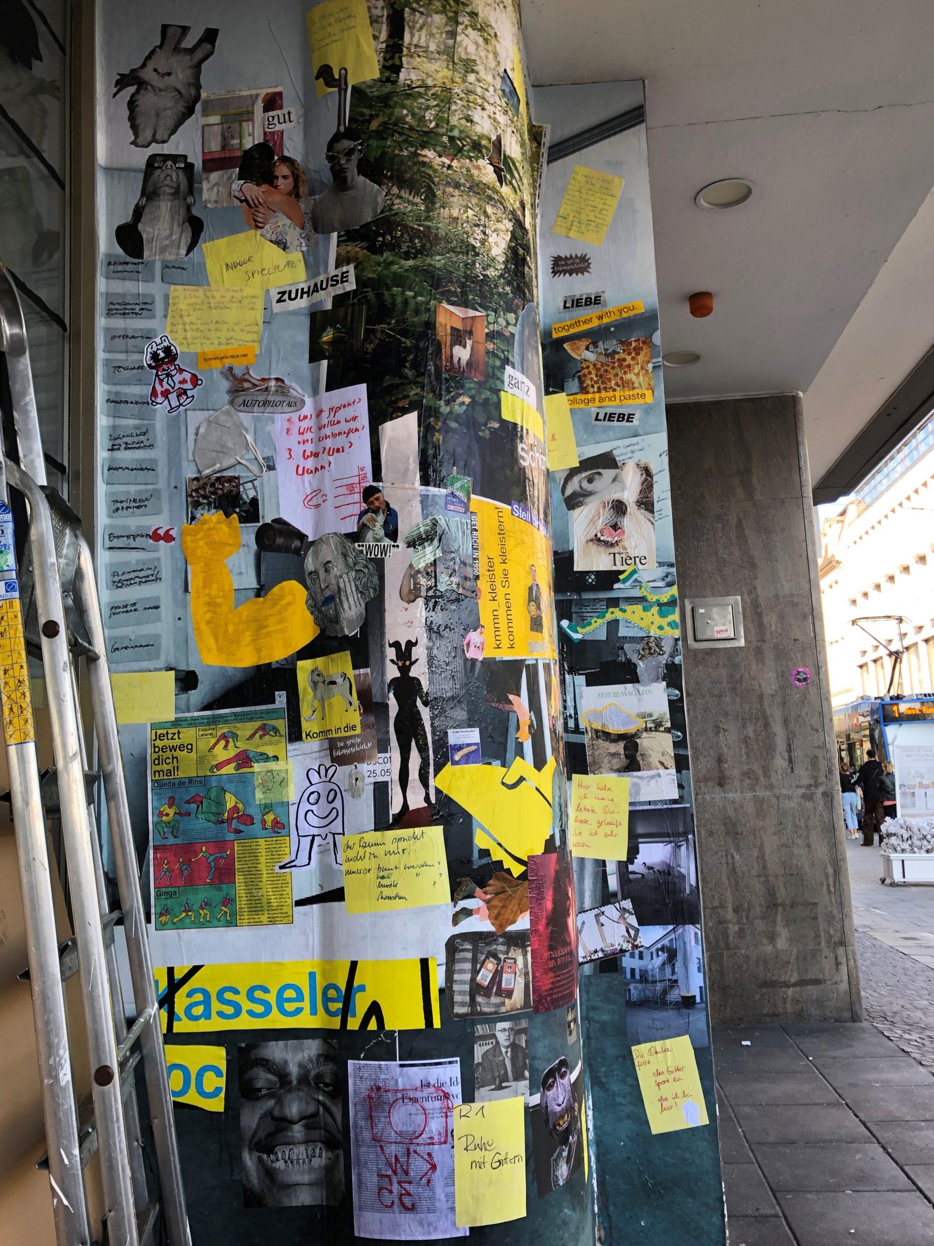 Das Foto zeigt eine Plakatsäule am Straßenrand, die vollkommen mit verschiedenen ausgeschnittenen Bildern, Texten und gelben Papierformen bedeckt ist.